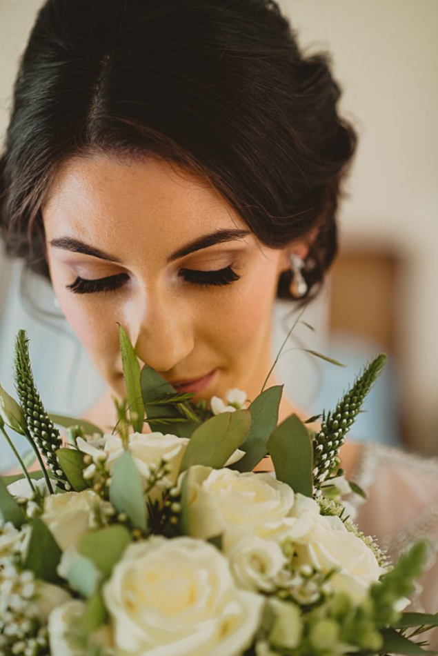 Beautiful bride with dark hair made up and holding bouquet of cream and green flowers